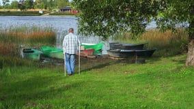 Άτομο με τα δεκανίκια που πηγαίνουν κοντά στα αλιευτικά σκάφη φιλμ μικρού μήκους