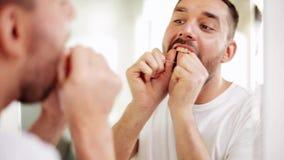 Άτομο με τα καθαρίζοντας δόντια οδοντικού νήματος στο λουτρό απόθεμα βίντεο