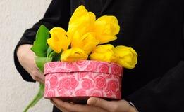 Άτομο με τα λουλούδια και το κιβώτιο δώρων Στοκ Φωτογραφίες
