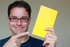 Άτομο με τα σκοτεινά γυαλιά που κρατά ένα κενό έγγραφο για τη διαφήμιση Στοκ εικόνα με δικαίωμα ελεύθερης χρήσης
