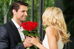Άτομο με τα τριαντάφυλλα που χρονολογούν την κυρία του στοκ φωτογραφία με δικαίωμα ελεύθερης χρήσης