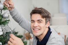 Άτομο με τα φω'τα νεράιδων που διακοσμεί το χριστουγεννιάτικο δέντρο Στοκ φωτογραφία με δικαίωμα ελεύθερης χρήσης