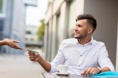 Άτομο με τα χρήματα δολαρίων που πληρώνει για τον καφέ στον καφέ Στοκ φωτογραφία με δικαίωμα ελεύθερης χρήσης