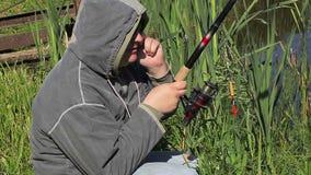 Άτομο με την αλιεία του τηλεφώνου ράβδων και κυττάρων στη λίμνη απόθεμα βίντεο