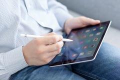 Άτομο με την εκμετάλλευση μολυβιών της Apple στο χέρι iPad υπέρ Στοκ φωτογραφία με δικαίωμα ελεύθερης χρήσης