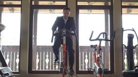 Άτομο με την κατάρτιση κοστουμιών στο στατικό ποδήλατο στη γυμναστική, σπάσιμο στην εργασία απόθεμα βίντεο