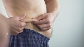 Άτομο με την κοιλιά μπύρας που εξετάζει τις πτυχές του, που εξετάζουν για να κάνει δίαιτα, προσοχή σωμάτων φιλμ μικρού μήκους