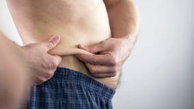 Άτομο με την κοιλιά μπύρας που εξετάζει τις πτυχές του, που εξετάζουν για να κάνει δίαιτα, προσοχή σωμάτων στοκ φωτογραφία με δικαίωμα ελεύθερης χρήσης