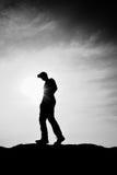 Άτομο με την κόκκινη ΚΑΠ στη δύσκολη αιχμή Άτομο που περπατά πέρα από τη δύσκολη σύνοδο κορυφής στον ήλιο Όμορφη στιγμή το θαύμα  Στοκ Εικόνες