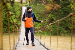Άτομο με την οδοιπορία σακιδίων πλάτης στο δάσος από την αρθρωμένη γέφυρα πέρα από τον ποταμό Κρύο weathe Πεζοπορία άνοιξη Ξύλινη στοκ φωτογραφία με δικαίωμα ελεύθερης χρήσης