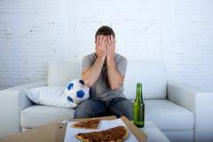 Άτομο με την πίτσα σφαιρών και ποδοσφαιρικό παιχνίδι προσοχής μπουκαλιών μπύρας στη TV που καλύπτει τα μάτια λυπημένα και που απο Στοκ εικόνες με δικαίωμα ελεύθερης χρήσης