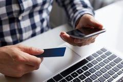 Άτομο με την πιστωτική κάρτα και το τηλέφωνο κατά να πληρώσει on-line Στοκ φωτογραφία με δικαίωμα ελεύθερης χρήσης
