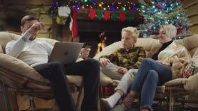 Άτομο με την πιστωτική κάρτα που ψωνίζει on-line στο lap-top ενώ λίγο δώρο Χριστουγέννων αφορά τη σύζυγο και το γιο του φιλμ μικρού μήκους