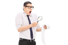 Άτομο με την πιό magnifier εξέταση έναν λογαριασμό στη δυσπιστία στοκ εικόνες