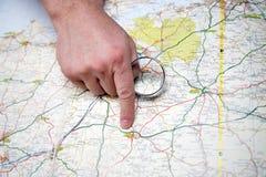 Άτομο με την πιό magnifier υπόδειξη σε έναν χάρτη στοκ φωτογραφία