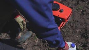 Άτομο με τη βενζίνη κοντά στον καλλιεργητή φιλμ μικρού μήκους