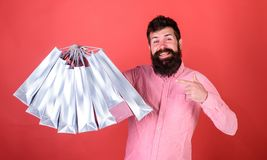 Άτομο με τη γενειάδα και mustache υπόδειξη στις τσάντες αγορών, κόκκινο υπόβαθρο Το Hipster στο ευτυχές πρόσωπο ψωνίζοντας εθίζει Στοκ Φωτογραφίες