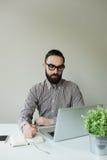 Άτομο με τη γενειάδα στα γυαλιά που παίρνουν τις σημειώσεις με το lap-top και το σημειωματάριο Στοκ εικόνες με δικαίωμα ελεύθερης χρήσης