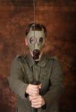 Άτομο με τη μάσκα αερίου και ξίφος katana στο καφετί υπόβαθρο μπατίκ Στοκ Εικόνες