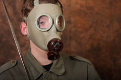 Άτομο με τη μάσκα αερίου και ξίφος katana στο καφετί υπόβαθρο μπατίκ Στοκ εικόνες με δικαίωμα ελεύθερης χρήσης