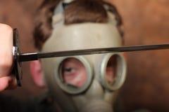 Άτομο με τη μάσκα αερίου και ξίφος katana στο καφετί υπόβαθρο μπατίκ Στοκ φωτογραφία με δικαίωμα ελεύθερης χρήσης