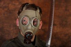 Άτομο με τη μάσκα αερίου και ξίφος katana στο καφετί υπόβαθρο μπατίκ Στοκ φωτογραφίες με δικαίωμα ελεύθερης χρήσης