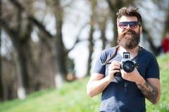 Άτομο με τη μακριά γενειάδα πολυάσχολη με τις φωτογραφίες πυροβολισμού Έννοια φωτογράφων Γενειοφόρος τρύγος λαβής φωτογράφων hips στοκ φωτογραφίες