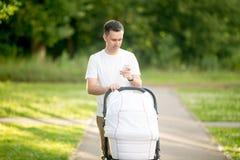 Άτομο με τη μεταφορά μωρών στο πάρκο που εξετάζει την τηλεφωνική οθόνη Στοκ φωτογραφία με δικαίωμα ελεύθερης χρήσης