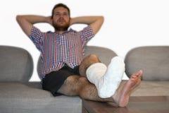 Άτομο με τη σπασμένη συνεδρίαση ποδιών στον καναπέ που μιλά στο κινητό τηλέφωνο Στοκ Φωτογραφίες