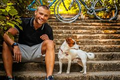 Άτομο με τη συνεδρίαση σκυλιών στα σκαλοπάτια στοκ εικόνες
