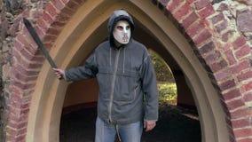 Άτομο με τη τρομακτική μάσκα αποκριών και μεγάλο μαχαίρι κοντά στις παλαιές πύλες φιλμ μικρού μήκους
