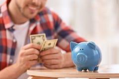 Άτομο με τη piggy τράπεζα και τα χρήματα στο σπίτι στοκ εικόνα