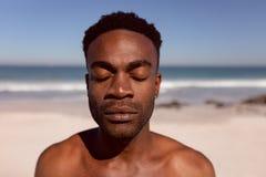Άτομο με τις προσοχές ιδιαίτερες στάση στην παραλία στην ηλιοφάνεια στοκ φωτογραφίες