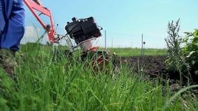 Άτομο με τον καλλιεργητή που προετοιμάζει το έδαφος για τη σπορά φιλμ μικρού μήκους