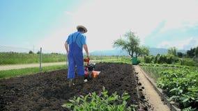 Άτομο με τον οργώνοντας κήπο καλλιεργητών σε αργή κίνηση απόθεμα βίντεο