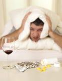 Άτομο με τον πονοκέφαλο και την απόλυση στο κρεβάτι με τις ταμπλέτες Στοκ φωτογραφία με δικαίωμα ελεύθερης χρήσης