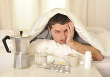 Άτομο με τον πονοκέφαλο και την απόλυση στο κρεβάτι με τις ταμπλέτες Στοκ Εικόνες