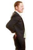 Άτομο με τον πόνο στην πλάτη που κρατά τα χέρια του στην πλάτη του Στοκ Φωτογραφίες