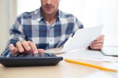 Άτομο με τον υπολογιστή που ελέγχει τους λογαριασμούς στοκ εικόνες με δικαίωμα ελεύθερης χρήσης