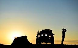 Άτομο με το αυτοκίνητο και σκηνή στο ηλιοβασίλεμα στοκ εικόνα με δικαίωμα ελεύθερης χρήσης
