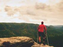 Άτομο με το δεκανίκι αντιβράχιων Πραγματοποιημένη η οδοιπόρος αιχμή βουνών με το σπασμένο πόδι ακινητοποιεί μέσα Στοκ Φωτογραφίες