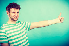 Άτομο με το επιδεμένο χέρι που παρουσιάζει αντίχειρα Στοκ Εικόνες