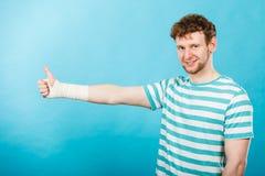 Άτομο με το επιδεμένο χέρι που παρουσιάζει αντίχειρα Στοκ Φωτογραφία