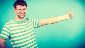 Άτομο με το επιδεμένο χέρι που παρουσιάζει αντίχειρα Στοκ εικόνα με δικαίωμα ελεύθερης χρήσης