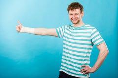 Άτομο με το επιδεμένο χέρι που παρουσιάζει αντίχειρα Στοκ Εικόνα