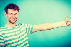 Άτομο με το επιδεμένο χέρι που παρουσιάζει αντίχειρα Στοκ Φωτογραφίες