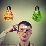Άτομο με το ερωτηματικό που σκέφτεται να εξετάσει επάνω το άχρηστο φαγητό και τα λαχανικά που διαμορφώνονται ως λάμπα φωτός Στοκ εικόνες με δικαίωμα ελεύθερης χρήσης