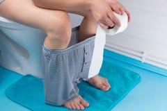 Άτομο, με το εσώρουχό του κάτω, που κάθεται στην τουαλέτα, με έναν ρόλο του χαρτιού τουαλέτας στοκ φωτογραφία