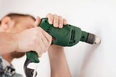 Άτομο με το ηλεκτρικό τρυπάνι που κάνει την τρύπα στον τοίχο στοκ φωτογραφία με δικαίωμα ελεύθερης χρήσης