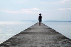 Άτομο με το καπέλο κάουμποϋ που στέκεται στο ηλιοβασίλεμα προσοχής γεφυρών Στοκ Εικόνες